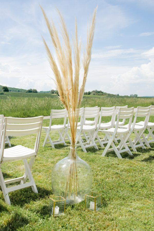 Freie Trauung mit weißen Stühlen und Weinballon mit Pampasgras im Vordergrund