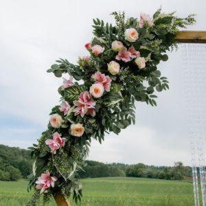 Großes, roséfarbenes Blumengesteck für den Traubogen