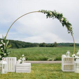 Runder Traubogen mit weißen Holzkisten und Blumenschmuck